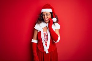 woman in Santa costume with tooth pain