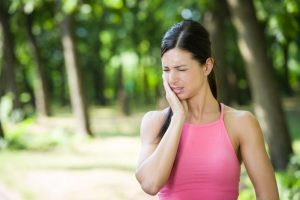 woman experiencing tooth pain while exercising outside